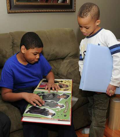 Matthew Bloom, 11, looks at a scrap album while his little brother Jacob, 6, looks on in their home on Monday Feb. 4, 2013 in Selkirk, N.Y.  (Lori Van Buren / Times Union) Photo: Lori Van Buren