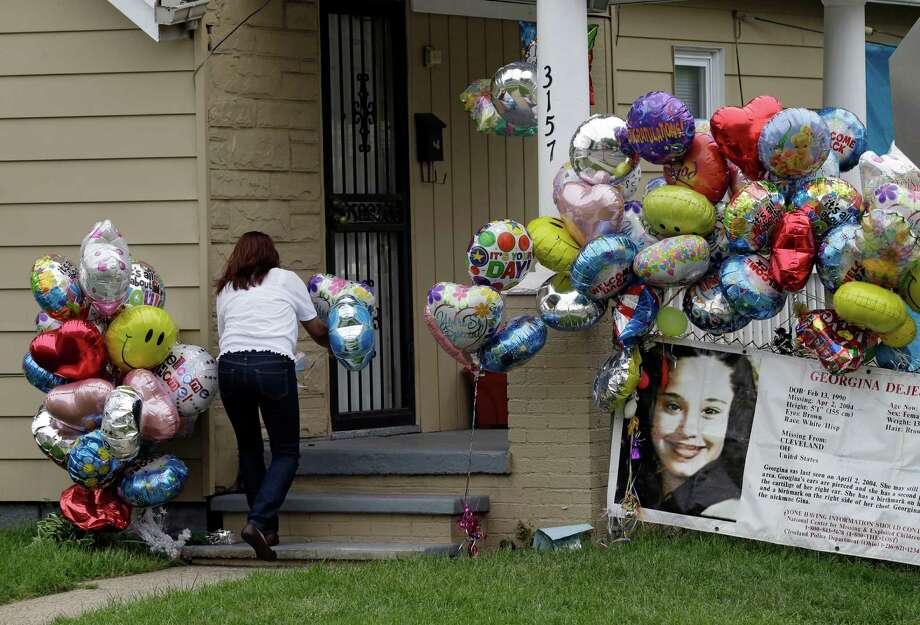 Culema Nevarez adds balloons to a growing tribute outside the hole of Gina DeJesus in Cleveland Friday, May 10, 2013. DeJesus was freed Monday from the home of Ariel Castro where she and two other women had been held captive for nearly a decade.  (AP Photo/Mark Duncan) Photo: Mark Duncan