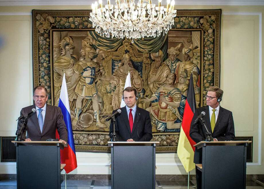 Russian Foreign Minister Sergei Lavrov (from left) and his counterparts from Poland, Radoslaw Sikorski, and Germany, Guido Westerwelle, give a joint news conference Friday in Warsaw, at which Lavrov said Russia is completing its delivery of surface-to-air missiles to Syria.