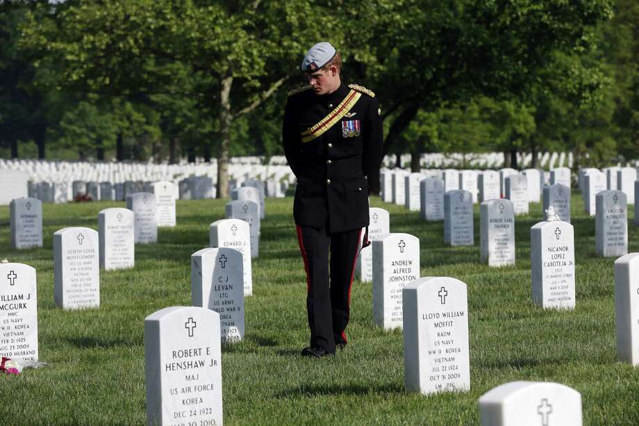Prince Harry walks among graves in Arlington National Cemetery. He is on a weeklong tour of the United States. Photo: Charles Dharapak / Getty Images