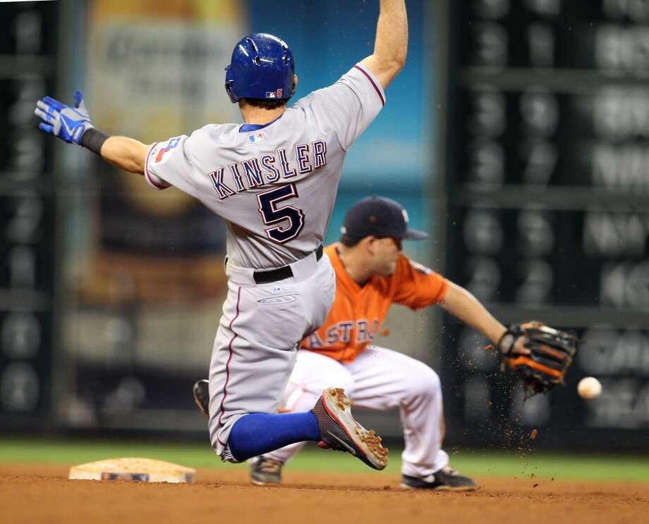 Ian Kinsler of the Rangers attempts to slide while Astros second baseman tries to make the tag in time.