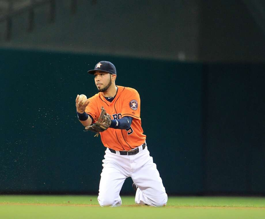 Marwin Gonzalez of the Astros fields a single hit by Ian Kinsler of the Rangers with his hand.