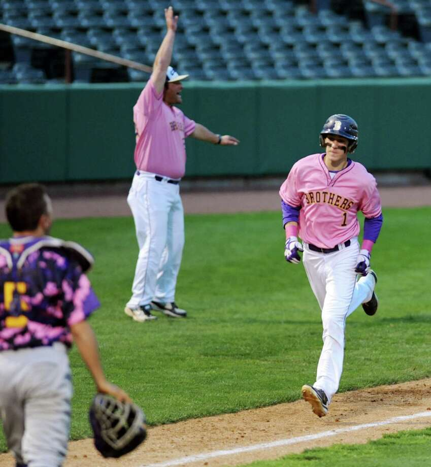CBA's Chase Crawford, right, receives the signal from coach Casey O'Connor to run home during their Coaches vs. Cancer baseball game against Troy on Friday, May 10, 2013, at Joseph L. Bruno Stadium in Troy, N.Y. (Cindy Schultz / Times Union) Photo: Cindy Schultz / 00022362A
