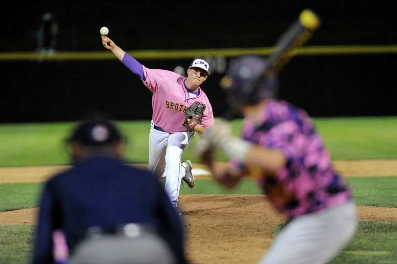 CBA's Ned Monthie, center, releases a pitch during their Coaches vs. Cancer baseball game against Tr
