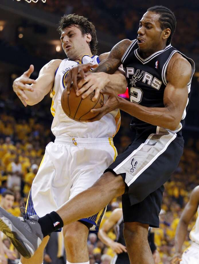 The Spurs' Kawhi Leonard and Warriors' Andrew Bogut grab for a rebound during first half action of Game 3 in the Western Conference semifinals Friday May 10, 2013 at Oracle Arena in Oakland, CA.