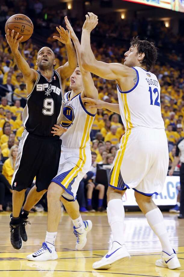 The Spurs' Tony Parker drives around the Warriors' Klay Thompson and Andrew Bogut during first half action of Game 3 in the Western Conference semifinals Friday May 10, 2013 at Oracle Arena in Oakland, CA.
