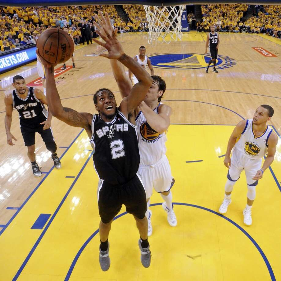 The Spurs' Kawhi Leonard shoots around the Warriors' Andrew Bogut during first half action of Game 3 in the Western Conference semifinals Friday May 10, 2013 at Oracle Arena in Oakland, CA.