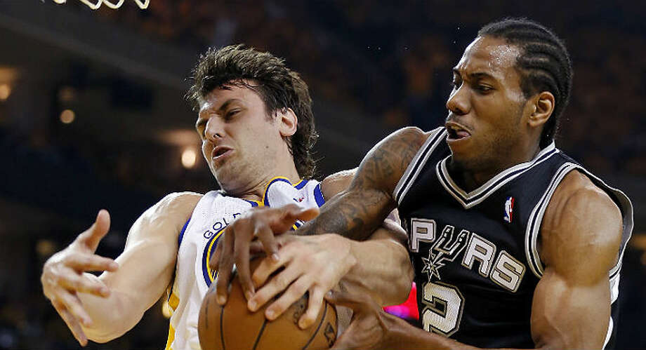 The Spurs' Kawhi Leonard and Warriors' Andrew Bogut grab for a rebound during Game 3 on Friday in Oakland. Edward A. Ornelas / San Antonio Express-News