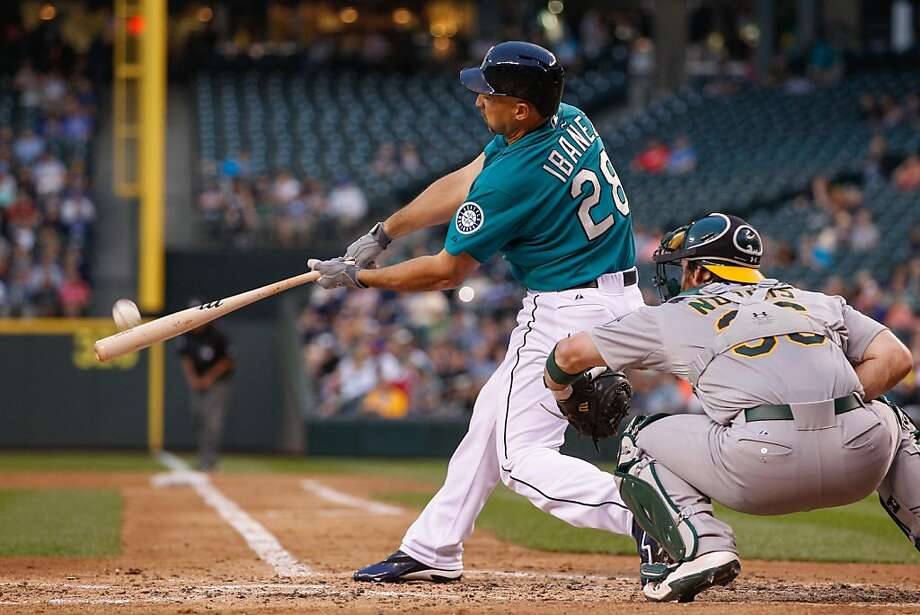 Raul Ibañez hits a three-run homer off Dan Straily in the third inning. The Mariners pulled within a half-game of the A's. Photo: Otto Greule Jr, Getty Images