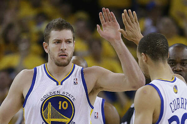 The Warriors' David Lee (left) celebrates with teammate Steph Curry after scoring in Friday's Game 3 in Oakland. Jeff Chiu / Associated Press