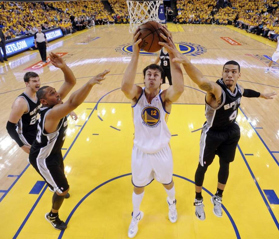 The Spurs' Tiago Splitter (from left), Boris Diaw and Danny Green defend the Warriors' Andrew Bogut during second half action of Game 3 in the Western Conference semifinals Friday May 10, 2013 at Oracle Arena in Oakland, CA. The Spurs won 102-92.
