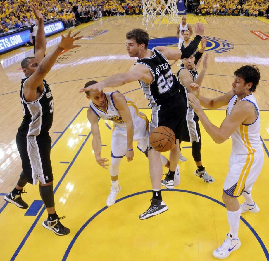 The Spurs' Boris Diaw and Tiago Splitter defend the Warriors' Stephen Curry as  he passes to the Warriors' Andrew Bogut during second half action of Game 3 in the Western Conference semifinals Friday May 10, 2013 at Oracle Arena in Oakland, CA. The Spurs won 102-92.