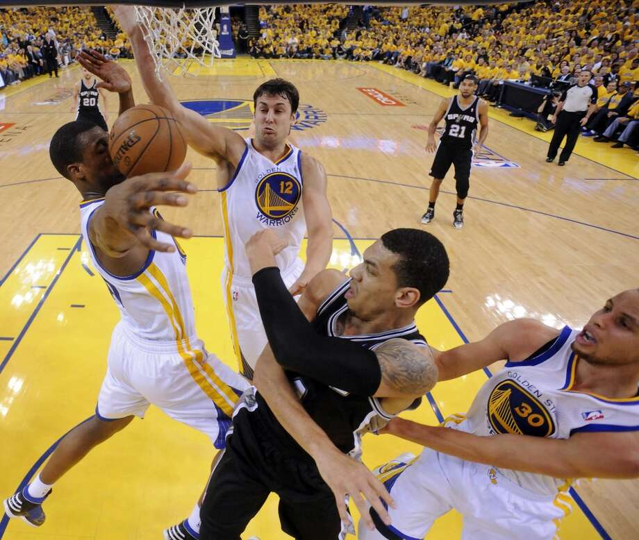San Antonio Spurs' Danny Green passes between Golden State Warriors' Harrison Barnes, Golden State Warriors' Andrew Bogut, and Golden State Warriors' Stephen Curry during first half action of Game 3 in the NBA Western Conference semifinals Friday May 10, 2013 at Oracle Arena in Oakland, CA.