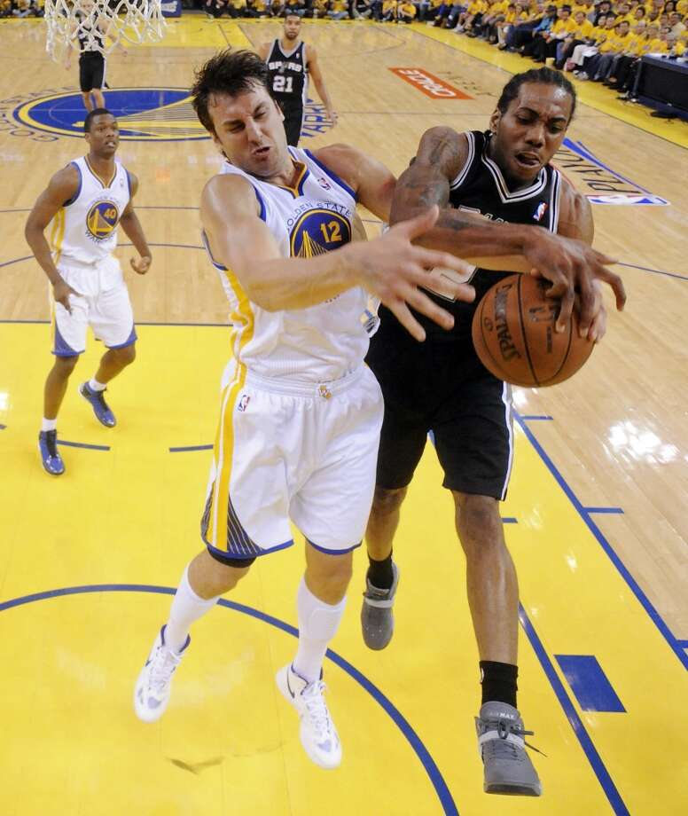 Golden State Warriors' Andrew Bogut and San Antonio Spurs' Kawhi Leonard grab for a rebound during first half action of Game 3 in the NBA Western Conference semifinals Friday May 10, 2013 at Oracle Arena in Oakland, CA.