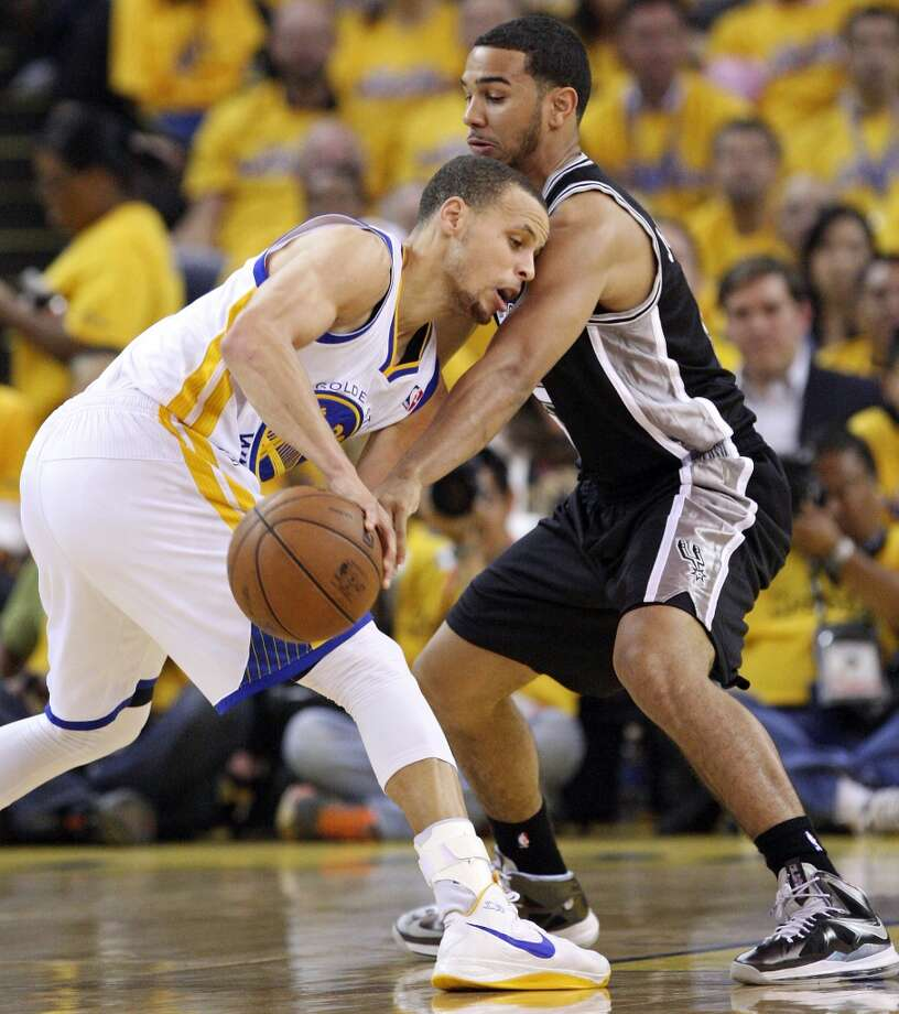 Golden State Warriors' Stephen Curry looks for room around San Antonio Spurs' Cory Joseph during first half action of Game 3 in the NBA Western Conference semifinals Friday May 10, 2013 at Oracle Arena in Oakland, CA.