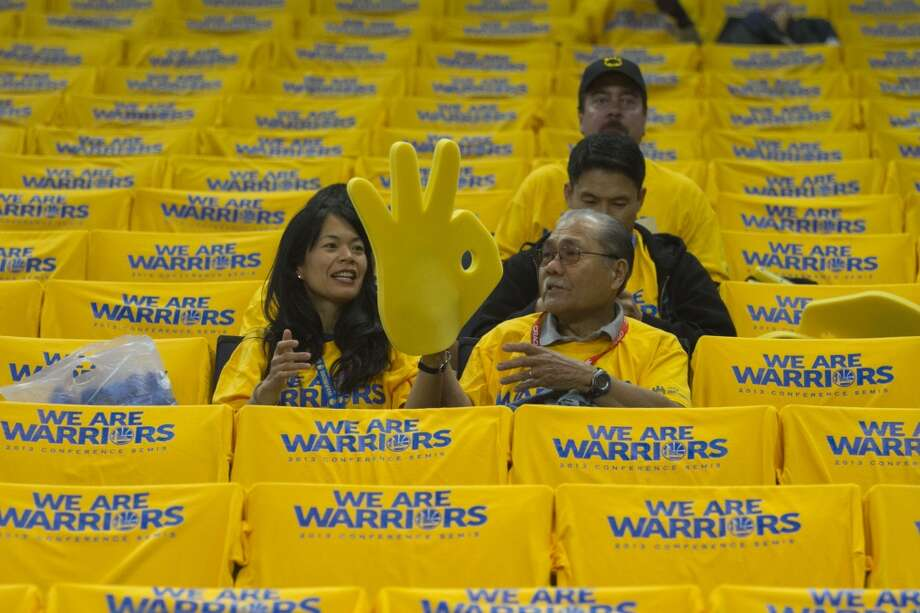 Marie Chang of Alameda looks at a large Warriors foam finder with her father Joe Tero, visiting from Bakersfield before the start of game 3 of the NBA Western Conference Semifinals between the Golden State Warriors and San Antonio Spurs at Oracle Arena, in Oakland, Calif. on May 10, 2013.