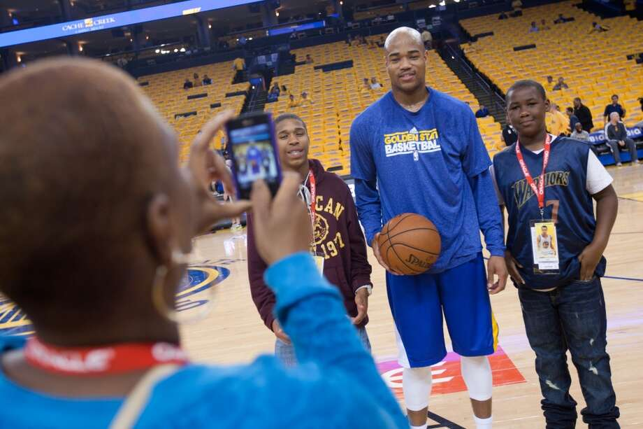 Torrell Gray and Richard Taylor stand with Warriors guard Jarrett Jack for a photograph from their mother Tammi Taylor before the start of game 3 of the NBA Western Conference Semifinals between the Golden State Warriors and  the San Antonio Spurs at Oracle Arena, in Oakland, Calif. on May 10, 2013.