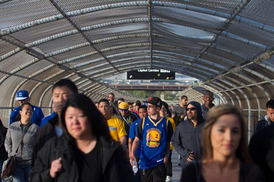 Fans walk across the pedestrian bridge from BART to Oracle Arena before the start of game 3 of the NBA Western Conference Semifinals between the Golden State Warriors and  the San Antonio Spurs in Oakland, Calif. on May 10, 2013.