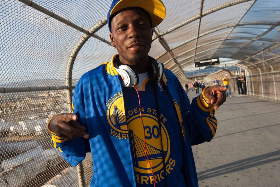 Duriel Evans of Oakland poses with some of his Golden State Warriors gear at the pedestrian bridge from BART to Oracle Arena before the start of game 3 of the NBA Western Conference Semifinals between the Golden State Warriors and  the San Antonio Spurs in Oakland, Calif. on May 10, 2013.