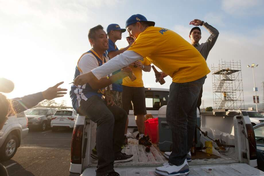(Left to right) Joey Salgado sits on the edge of a pickup truck as his brother John Salgado hands over a bottle opener, while friend Justin Olivio looks on while they tailgate before the start of game 3 of the NBA Western Conference Semifinals between the Golden State Warriors and  the San Antonio Spurs at Oracle Arena, in Oakland, Calif. on May 10, 2013.