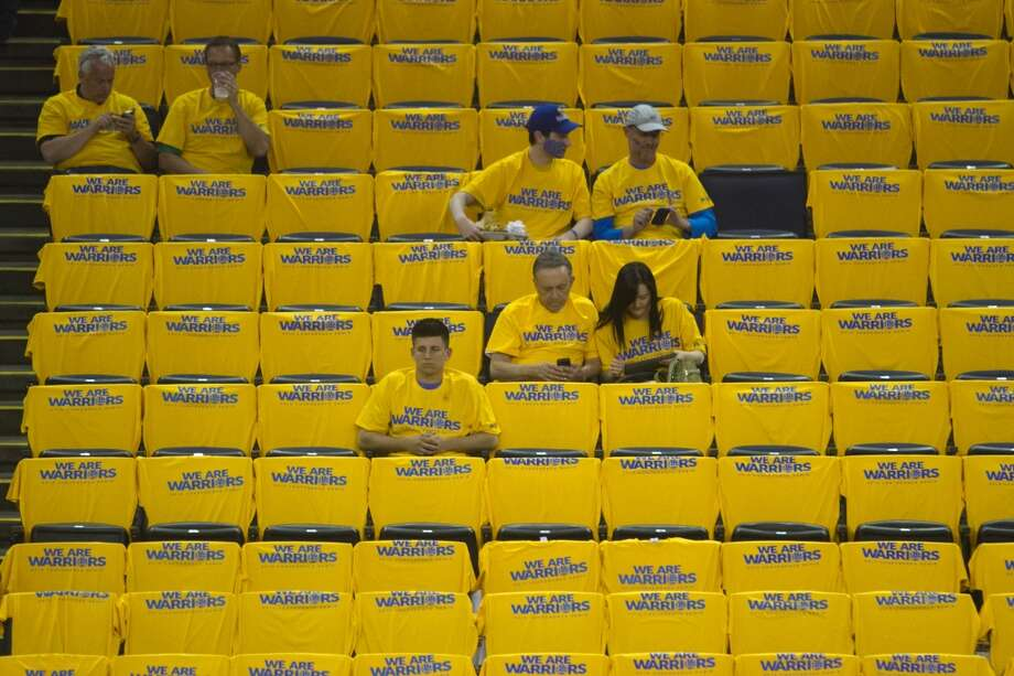 "A Golden State Warriors fan fill into the Oracle Arena and don yellow t-shirts with ""We Are Warriors""  emblazoned on them before game 3 of the NBA Western Conference Semifinals against the San Antonio Spurs at Oracle Arena, in Oakland, Calif. on May 10, 2013."