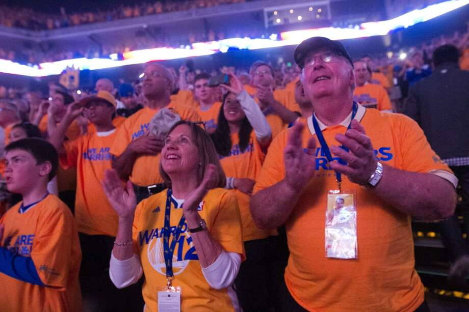 (Left to right) Sue and Stephen Coates of Los Gatos cheer as the national anthem starts before the start of game 3 of the NBA Western Conference Semifinals between the Golden State Warriors and  the San Antonio Spurs at Oracle Arena, in Oakland, Calif. on May 10, 2013.