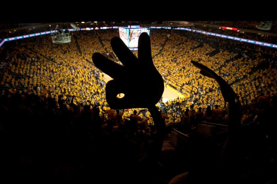 A Golden State Warriors fan holds a giant foam Warriors finger while cheering in game 3 of the NBA Western Conference Semifinals at Oracle Arena, in Oakland, Calif. on May 10, 2013.