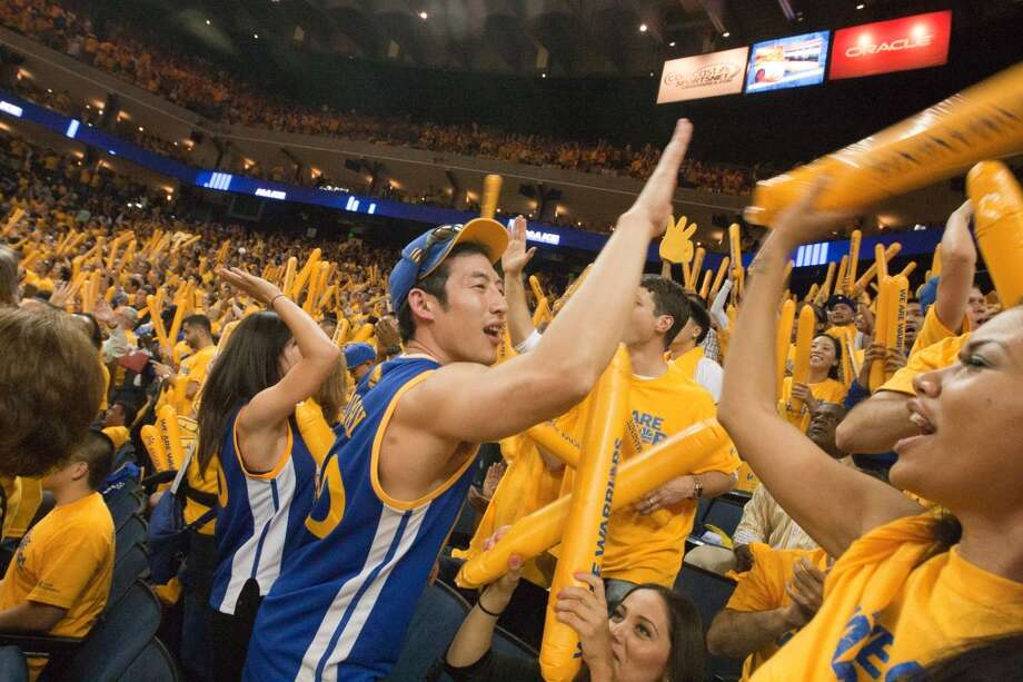 Golden State Warriors fan Ben Jiang of Oakland high-fives another fan after the Warriors tied the the San Antonio Spurs during the third quarter of game 3 of the NBA Western Conference Semifinals at Oracle Arena, in Oakland, Calif. on May 10, 2013.