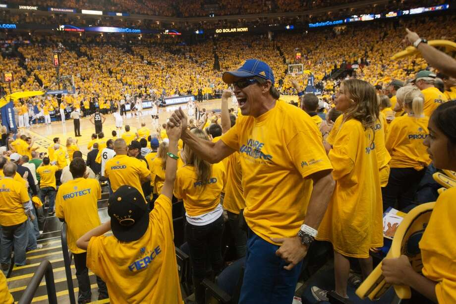 Golden State Warriors fan Tom Knight of San Ramon high fives his son Corbin, 7, while watching the Warriors play the San Antonio Spurs in game 3 of the NBA Western Conference Semifinals at Oracle Arena, in Oakland, Calif. on May 10, 2013.
