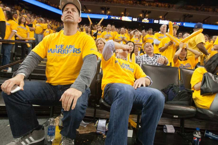 Golden State Warriors fans (left to right) Chester Aldridge and J.J. Davis, both of San Rafael, reacts to a missed shot by the Warriors in the last minutes of game 3 of the NBA Western Conference Semifinals against the San Antonio Spurs at Oracle Arena, in Oakland, Calif. on May 10, 2013.