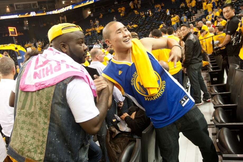 Austin Kwon, right, of San Jose has his picture taken with rapper Mistah Fab after game 3 of the NBA Western Conference Semifinals between the Golden State Warriors and  the San Antonio Spurs at Oracle Arena, in Oakland, Calif. on May 10, 2013.