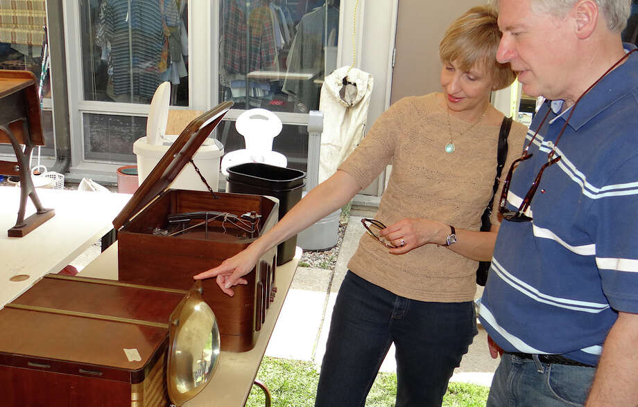Monika Pfeiffer and Bob Donais of Windsor check out a vintage television set Friday at the United Methodist Church's annual tag sale. Photo: Mike Lauterborn / Westport News contributed