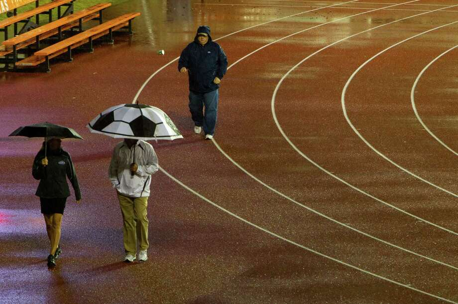 Attendees walk with their umbrellas during a rain delay during the UIL High School State Track Meet at Mike A. Myers Stadium Friday, May 10, 2013, in Austin. Photo: Cody Duty, Houston Chronicle / © 2013 Houston Chronicle