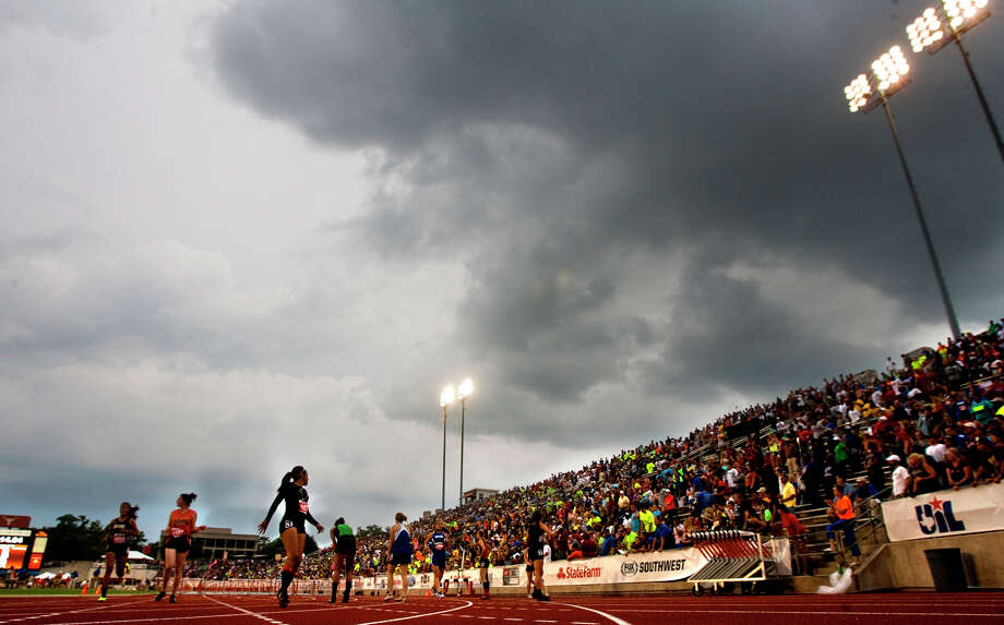 Rain clouds form over Mike A. Myers Stadium as athletes finish the 1A Girls 100 Meter hurdles at the UIL High School State Track meet Friday, May 10, 2013, in Austin. The meet faced a rain delay as lightning moved into the area. Photo: Cody Duty, Houston Chronicle / © 2013 Houston Chronicle