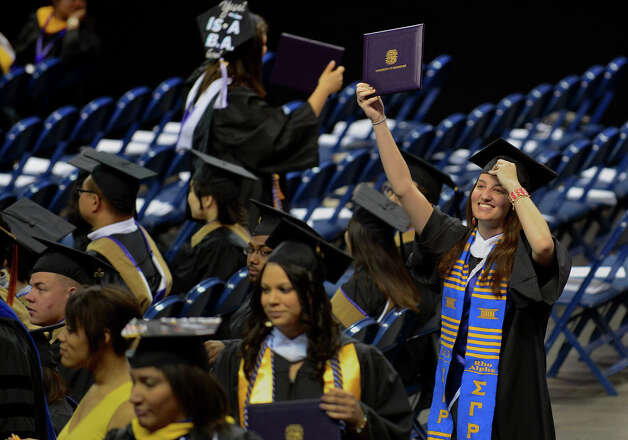 University of Bridgeport graduate Kaitlin O'Connell waves her diploma as she walks back to her seat, during the school's 103rd Commencement Ceremony held at the Webster Bank Arena in Bridgeport, Conn. on Saturday May 11, 2013. Photo: Christian Abraham / Co