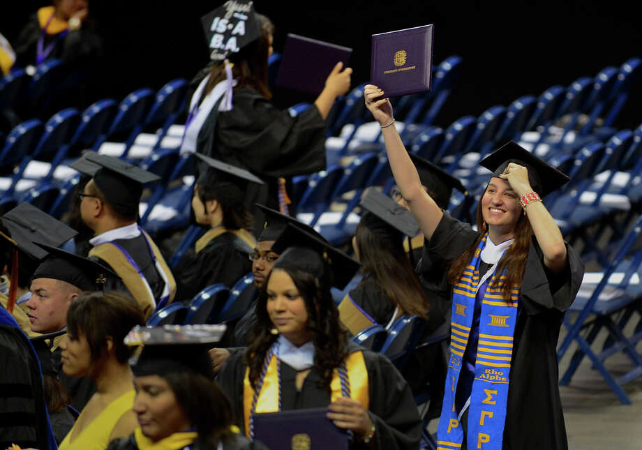 University of Bridgeport graduate Kaitlin O'Connell waves her diploma as she walks back to her seat, during the school's 103rd Commencement Ceremony held at the Webster Bank Arena in Bridgeport, Conn. on Saturday May 11, 2013. Photo: Christian Abraham / Connecticut Post