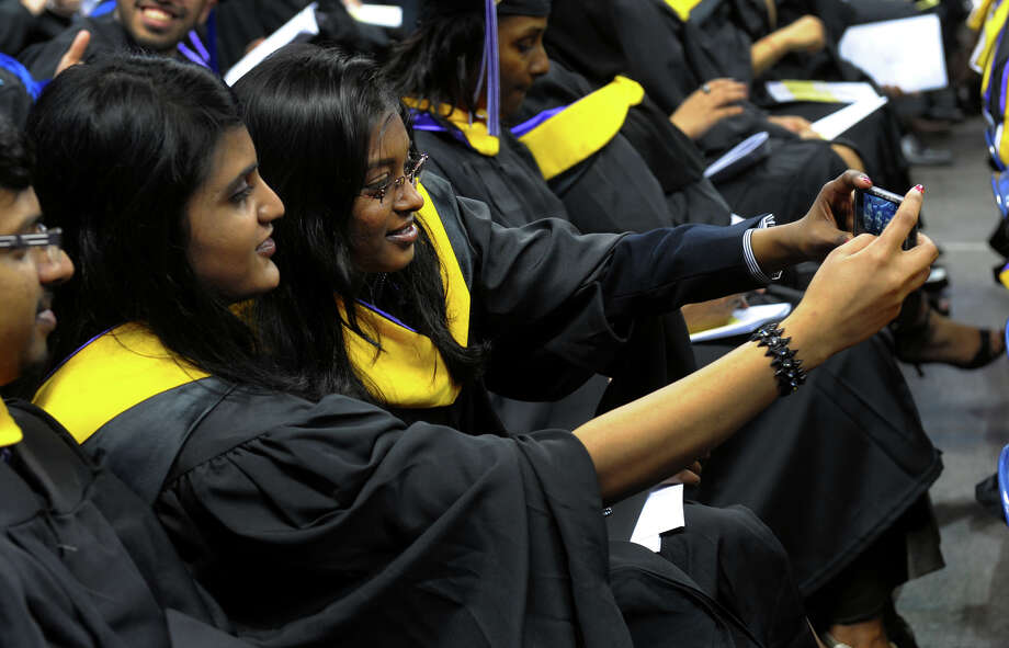 University of Bridgeport graduates Srujana Kumari Sripathi and her friend Karthik Yelakanti, in front, take pitures of themselves, during the school's 103rd Commencement Ceremony held at the Webster Bank Arena in Bridgeport, Conn. on Saturday May 11, 2013. Photo: Christian Abraham / Connecticut Post