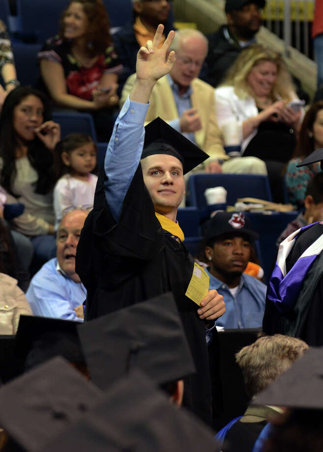 University of Bridgeport graduate Holden Hassell, of Long Island, NY, waves to his family before going up for his diploma, during the school's 103rd Commencement Ceremony held at the Webster Bank Arena in Bridgeport, Conn. on Saturday May 11, 2013. Photo: Christian Abraham / Connecticut Post