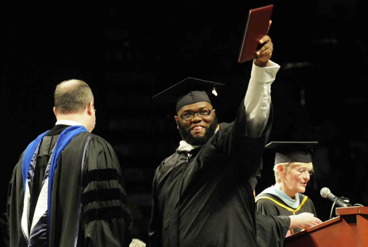 Graduate Daniel A. Cobbins holds up his degree as he walks the stage during The College of St. Rose 90th Annual Commencement at the Times Union Center on Saturday May 11, 2013 in Albany, N.Y. (Michael P. Farrell/Times Union)