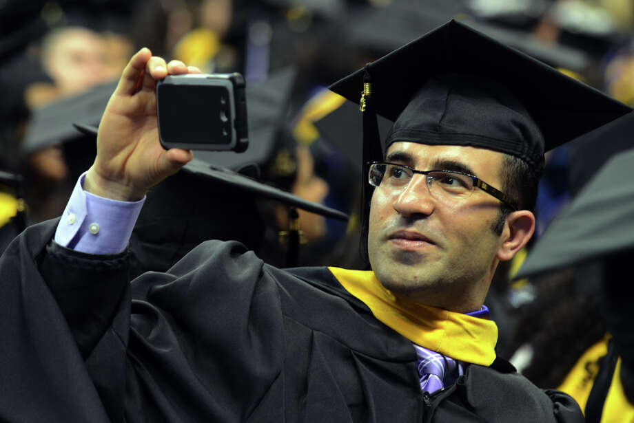 University of Bridgeport graduate Dleer Saber makes a video with his smart phone, during the school's 103rd Commencement Ceremony held at the Webster Bank Arena in Bridgeport, Conn. on Saturday May 11, 2013. Photo: Christian Abraham / Connecticut Post