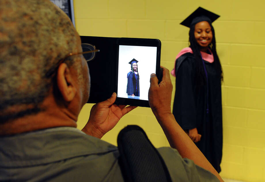 Graduate Kim Leak, of Coram, NY, poses for a photo taken by her dad Hillis, during University of Bridgeport's 103rd Commencement Ceremony held at the Webster Bank Arena in Bridgeport, Conn. on Saturday May 11, 2013. Photo: Christian Abraham / Connecticut Post