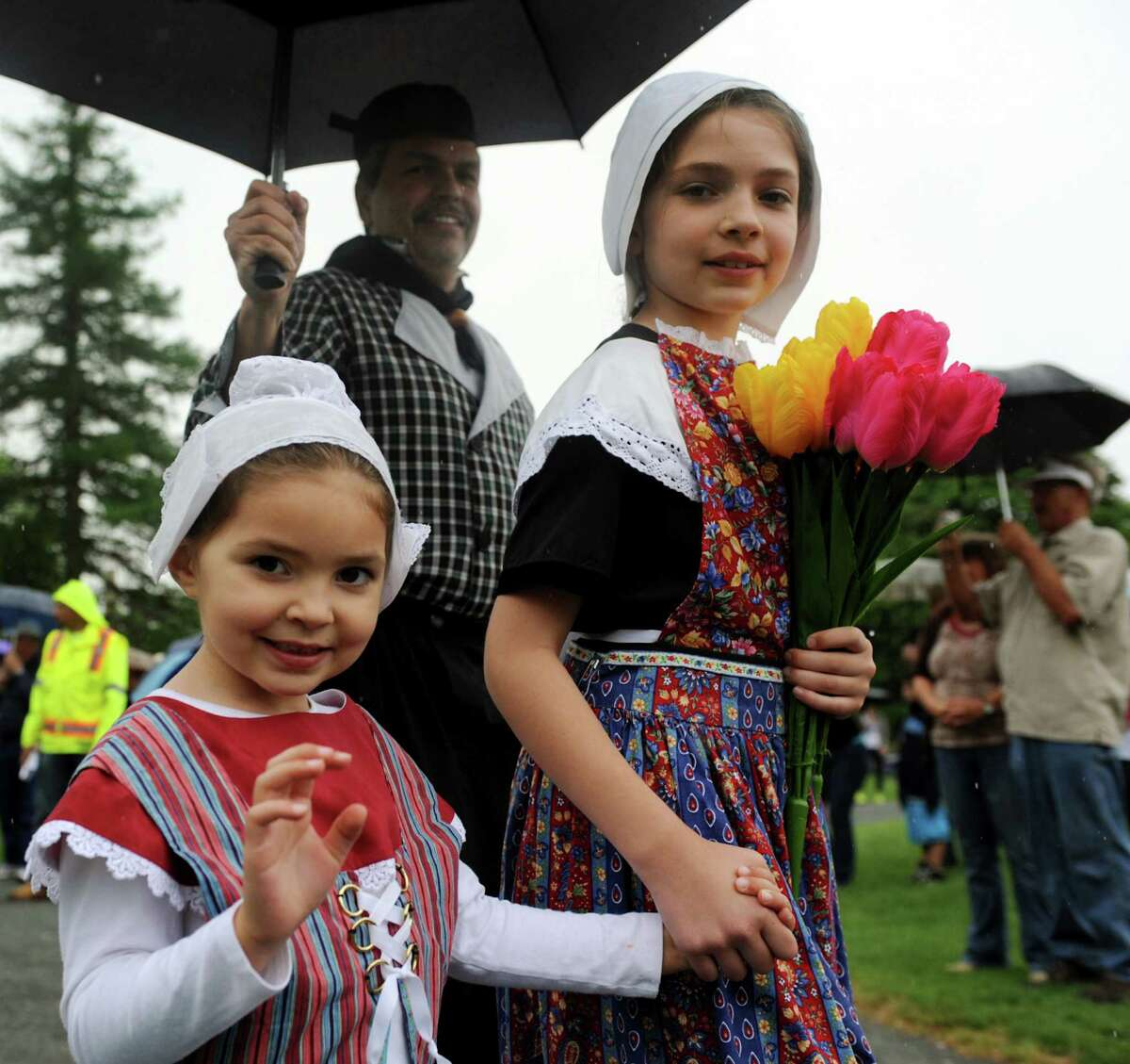 Callista Schermerhorn, 4, left, and her sister Alexandra, 10, walk with the Dutch Settlers Society as they parade toward the coronation during the Tulip Festival on Saturday, May 11, 2013, at Washington Park in Albany, N.Y. (Cindy Schultz / Times Union)
