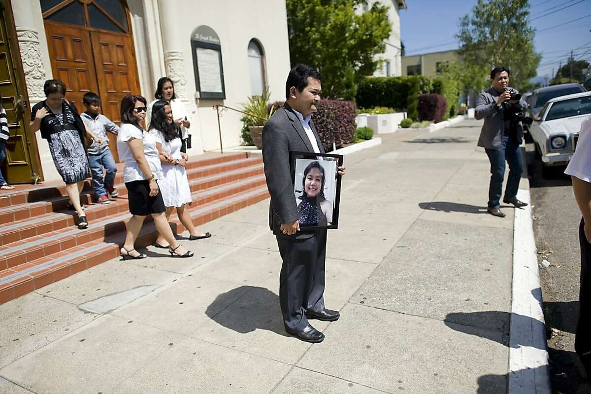 Aldrin Geronga holds a picture of his wife as he watches pallbearers place her ashes into a hearse following memorial services at St. Joseph Basilica. The family of Felomina Geronga, one of the five women who died in a limousine fire last weekend on the San Mateo Bridge, held a Catholic Mass memorial for her at St. Joseph Basilica in Alameda, CA Saturday May 11th, 2013.