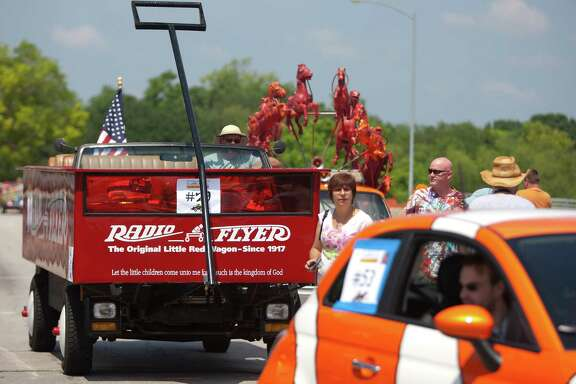 Ted Mangum's Radio Flyer Wagon lines up with about 300 artful vehicles of all shapes and sizes down Allen Parkway during the 26th annual Houston Art Car Parade May 11, 2013, in Houston.  The parade, produced by the Orange Show is the largest art car parade in the world.