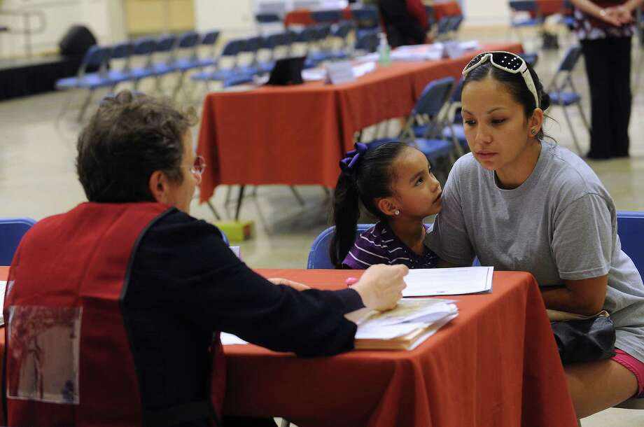 Melanie Mendoza and her daughter, Jayden Quiroga, listen as Roberta Sparks explains some points about Pre-K 4 SA at a fair at the South San Antonio Independent School District facility at 4622 Ray Ellison Drive on Wednesday, May 8, 2013. Photo: Billy Calzada, San Antonio Express-News / San Antonio Express-News
