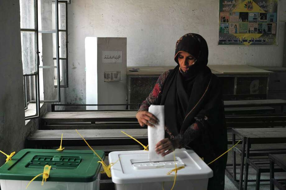 A woman casts her vote at a polling station in the city of Wagah, Pakistan, May 11, 2013. Pakistanis went to the polls in high numbers on Saturday, in a vote that carried the historic prospect of the country's first fully democratic political cycle despite fresh violence from Taliban insurgents. (Tyler Hicks/The New York Times) Photo: TYLER HICKS / NYTNS