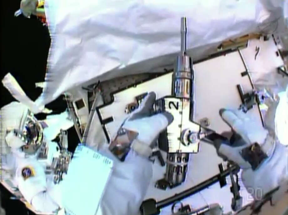 In this image made from video provided by NASA, astronaut Christopher Cassidy, foreground, holds a power wrench as he stows away a suspect coolant pump on the International Space Station on Saturday, May 11, 2013. Thomas Marshburn is at left. The two astronauts made the spacewalk to replace the pump after flakes of frozen ammonia coolant were spotted outside the station on Thursday. (AP Photo/NASA)