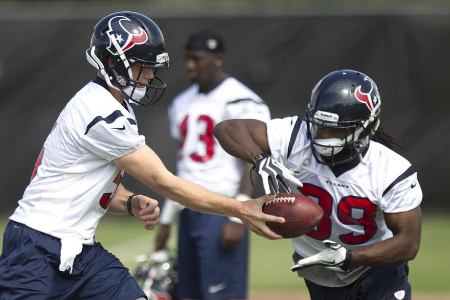 Texans quarterback Collin Klein hands the ball off to running back Deji Karim.