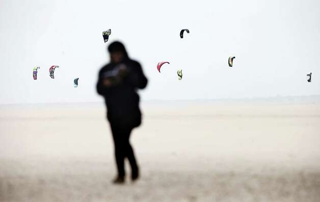 A person walks on the beach as kite surfers enjoy the strong southwest wind, in Maasvlakte, the Netherlands, on May 10, 2013. In the coming days the nice weather will be disturbed by clouds and rain. Photo: JERRY LAMPEN, AFP/Getty Images / AFP