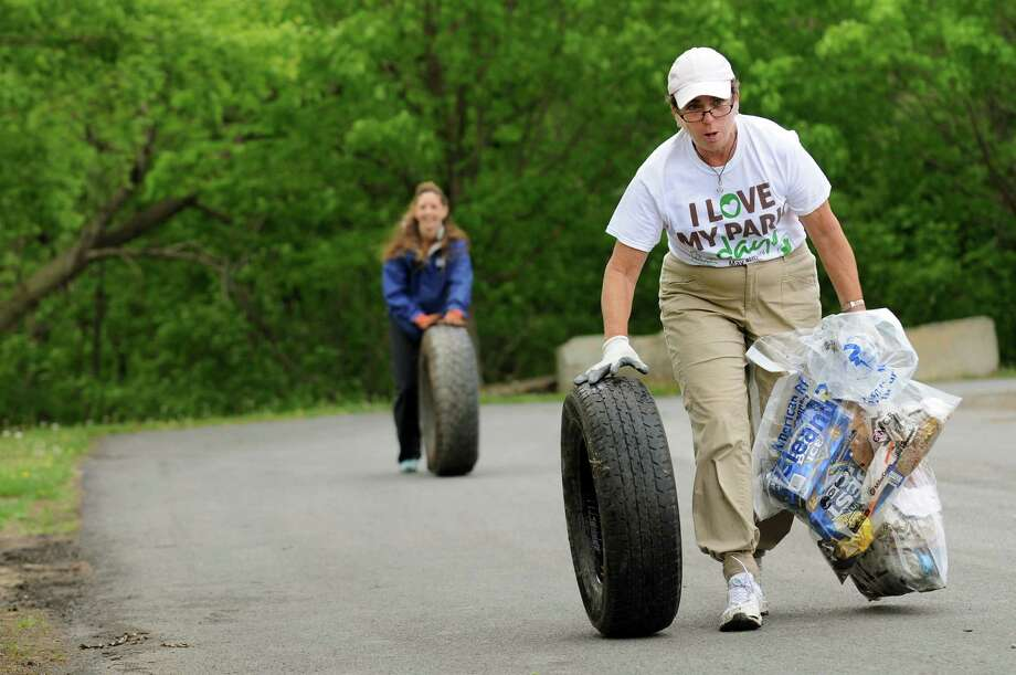 Mary Thibodeau, right, and Myra Fedyniak, both of Albany roll discarded tires as they help clean up garbage along the Hudson River on Saturday, May 11, 2013, at the Resselaer Boat Launch in Rensselaer, N.Y. The Capital District Volunteers group organized the local effort which as part of the 2nd annual Riverkeeper Sweep. (Cindy Schultz / Times Union) Photo: Cindy Schultz / 00022356A